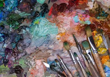 artists brushes and oil paints on wooden palette. macro artist's palette, texture mixed oil paints in different colors and saturation. palette with paintbrush and palette-knife